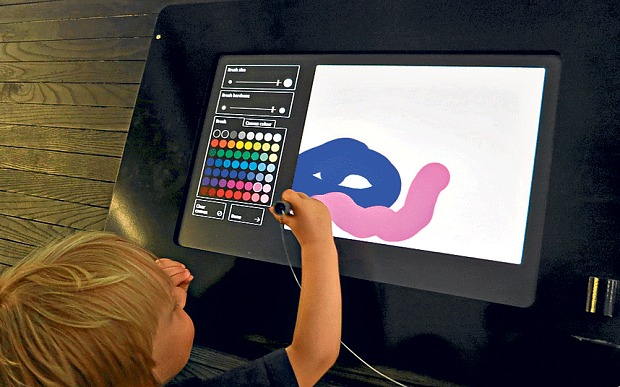 "Child in the exhibition ""Henri Matisse: The Cut-Outs"" at the Tate Modern, drawing on a touch screen."