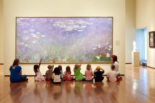 children in museum raising hands